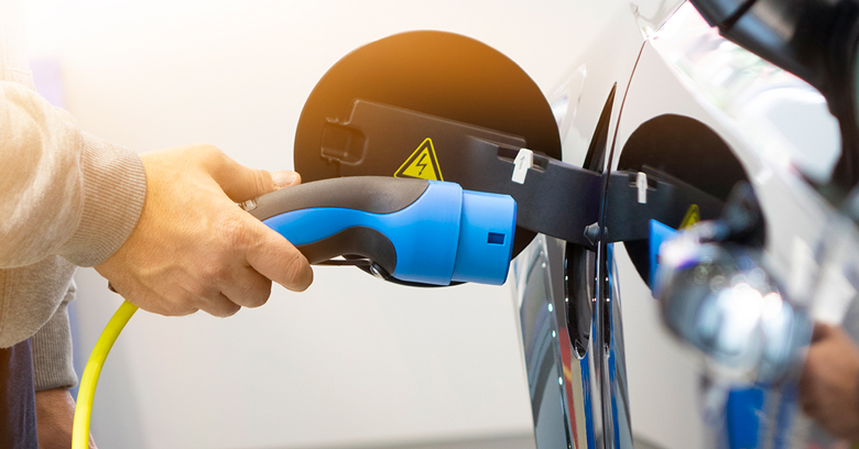 A man charging an electric vehicle