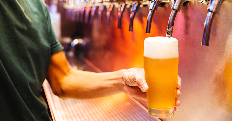 Barman tapping a glass of draft beer