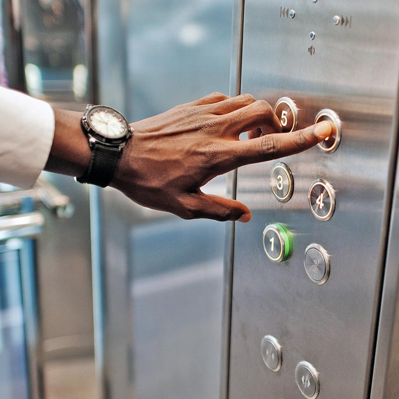 Man's hand pressing elevator buttons